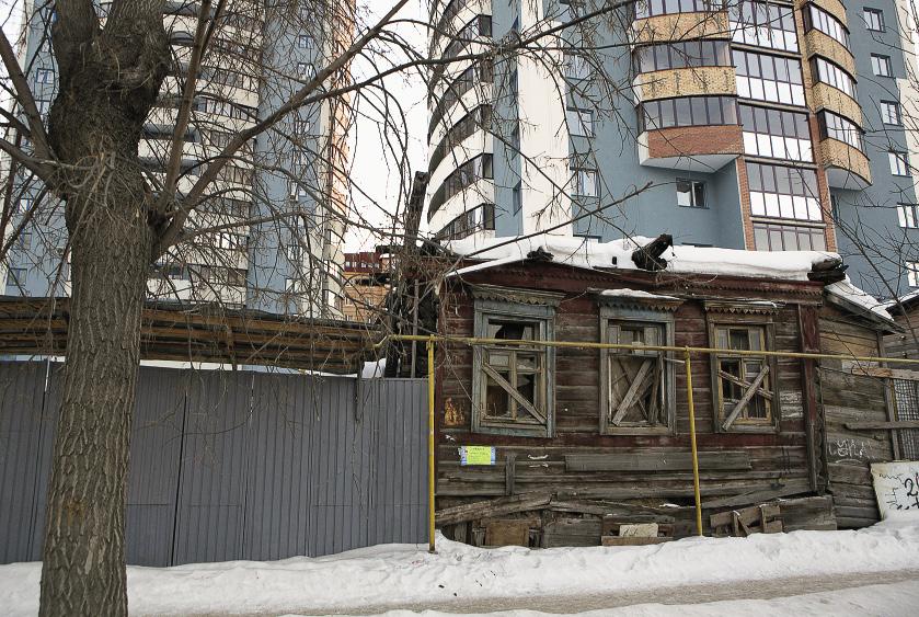 Деревянные домики на фоне многоэтажных новостроек