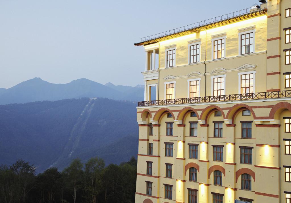 Вечером подсвеченное здание отеля красиво смотрится на фоне гор. Сочи. Краснодарский край.