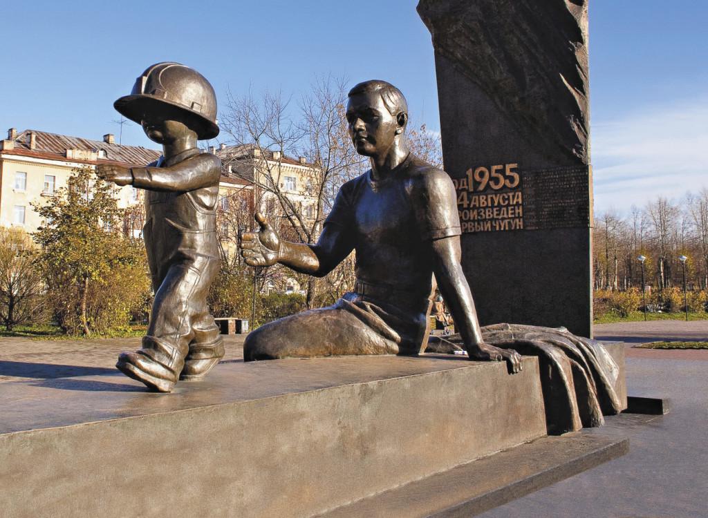 Памятник металлургам, символ преемственности поколений состоит из двух фигур – металлург-отец и сын в папиной каске, который идет к металлургическому заводу.