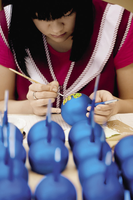 Сотрудница ОАО «Елочка» работает в цехе росписи елочных игрушек.