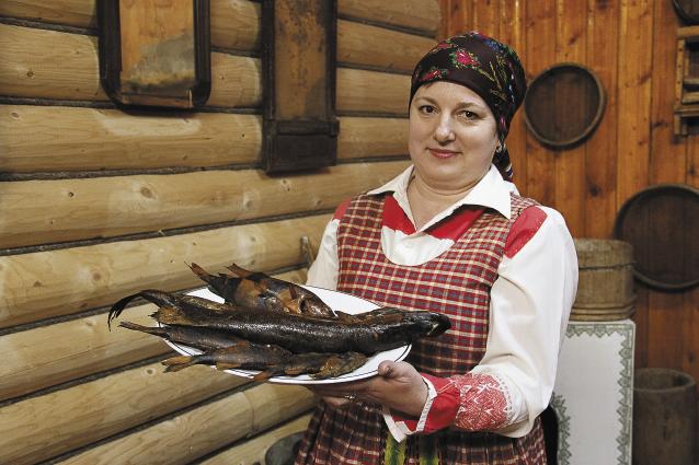 Официантка несет для гостей свежепойманную рыбу – сразу после коптильни.